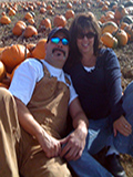 picture of owners in a pumpking patch, embracing